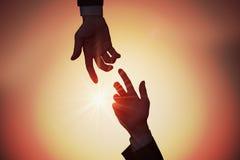 Принципиальная схема помощи и помощи 2 руки достигают один другого на заходе солнца стоковые фото
