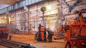 принципиальная схема промышленная Кран положенный вниз с оранжевой детали на пол и работника человека принимая ее стоковые фотографии rf