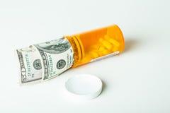 Принципиальные схемы деньги и отпускаемые по рецепту лекарства в контейнере с 100 счетами доллара стоковое изображение rf