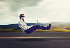 принципиальная схема голодает интернет Levitating бизнесмен на дороге используя портативный компьютер Стоковое Фото