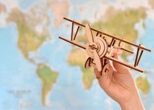 Принципиальная схема перемещения и туризма самолет игрушки удерживания руки против карты мира Стоковое фото RF