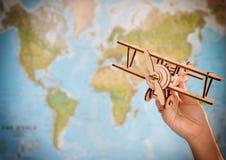 Принципиальная схема перемещения и туризма самолет игрушки удерживания руки против карты мира Стоковые Изображения