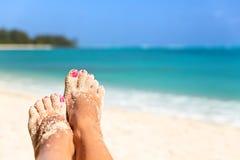 Принципиальная схема праздника Конец-вверх ног женщины ослабляя на пляже, наслаждаясь Стоковое Фото