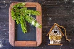 Принципиальная схема рождества. Винтажная доска мелка, елевые ветви и birdhouse Стоковое Изображение RF