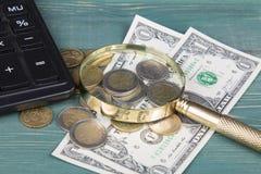 принципиальная схема финансовохозяйственная Калькулятор, лупа, монетки евро и долларовые банкноты на таблице древесной зелени Стоковая Фотография RF