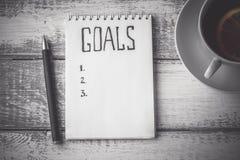 Принципиальная схема целей Тетрадь с целями перечисляет, чашка чаю на деревянном столе Мотивация Стоковое Изображение RF