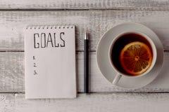 Принципиальная схема целей Тетрадь с целями перечисляет, чашка чаю на деревянном столе Мотивация Стоковое фото RF
