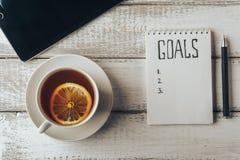 Принципиальная схема целей Тетрадь с целями перечисляет, tablet чашку чаю на деревянном столе Стоковое Фото