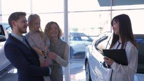 Приобретение автомобиля, молодая радостная семья с ребенком покупает машину и женщина менеджера азиатская дает ключи рук на автом акции видеоматериалы