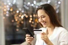 Приобретение девушки на линии с кредитной карточкой и телефоном дома стоковая фотография rf