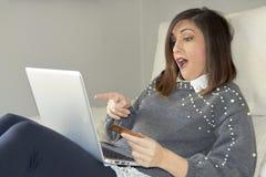 Приобретение женщины с ноутбуком на софе стоковые фото