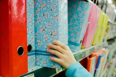 Приобретение канцелярских принадлежностей, руки ` s детей вытягивает от полки папки магазина для бумаг в руках покупателя стоковое изображение rf