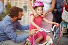 Приобретение матери на счастливом шлеме велосипеда девушки в магазине велосипеда стоковое изображение