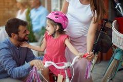 Приобретение семьи на счастливом шлеме велосипеда девушки в магазине велосипеда стоковые фото
