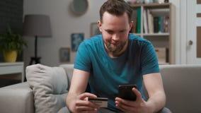 Приобретение человека онлайн, используя смартфон и кредитную карточку дома, ходя по магазинам приложение мобильного телефона Счас видеоматериал
