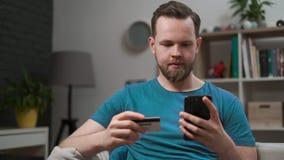 Приобретение человека онлайн, используя смартфон и кредитную карточку дома, ходя по магазинам приложение мобильного телефона Кред сток-видео