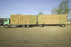 Припаркованная тележка нагрузила с опрятно штабелированными связками сена стоковые фото