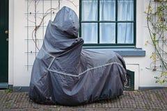 Припаркованное мотоцилк с голубым защитным чехлом Стоковые Фотографии RF