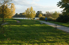 Припаркуйте с путем к реке и человеку идя на заход солнца осени Стоковые Фото