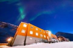 Приполюсная ледовитая звезда неба borealis snowscooter рассвета северного сияния в Норвегии Свальбарде в Longyearbyen горы луны стоковое изображение