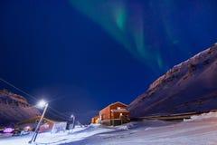 Приполюсная ледовитая звезда неба borealis snowscooter рассвета северного сияния в Норвегии Свальбарде в Longyearbyen горы луны стоковое изображение rf
