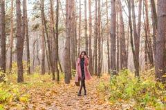 Приправьте, падение и концепция людей - красивая молодая женщина идя в парк осени стоковое изображение rf