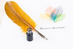 Приправьте сообщение приветствиям ` s на ручке бумаги и quill хлопка Стоковые Изображения