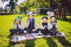 Природа праздников семьи темы активная дети людей группы небольшие маленькие 3 брать и сестра сидят onblanket близко стоковые фото