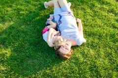 природа семьи счастливая Дочь младенца мамы и малыша кладя и ослабляя, обнимая, на луге зеленой травы на заходе солнца вечера пот Стоковые Фото