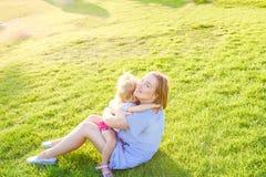 природа семьи счастливая Дочь младенца мамы и малыша ослабляя, обнимающ, смеющся над и имеет потеху на луге зеленой травы на выра Стоковая Фотография RF