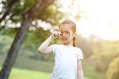 Природа азиатской маленькой девочки исследуя с стеклом увеличителя на переплюнет стоковое фото