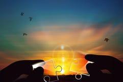 Присоединение к 2 частей стеклянной головоломки против предпосылки захода солнца стоковые фото