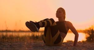 Приспособленная здоровая женщина протягивая на циновке йоги на взморье пляжа, делая хрусты тренировки подбрюшные, тренировку и об видеоматериал