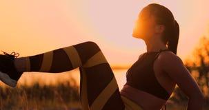 Приспособленная здоровая женщина протягивая на циновке йоги на взморье пляжа, делая хрусты тренировки подбрюшные, тренировку и об акции видеоматериалы