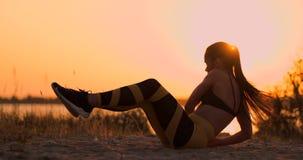 Приспособленная здоровая женщина протягивая на циновке йоги на взморье пляжа, делая хрусты тренировки подбрюшные, тренировку и об сток-видео