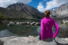 Приспособленная привлекательная женщина сидит самостоятельно озером каторжник в весеннем времени, расположенном US-395, около мам стоковые фото