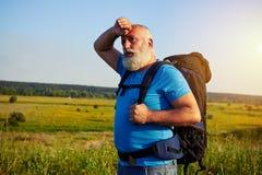 Приспособьте постаретого человека при рюкзак стоя в поле и обтирая его Стоковые Изображения RF