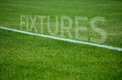Приспособления футбола отправляют СМС на траве с белой майной Стоковые Фотографии RF