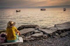 Пристальные взгляды женщины через озеро Ohrid на заходе солнца стоковое изображение