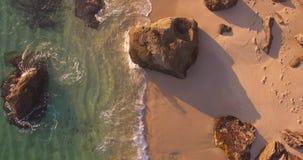 Пристаньте воздушную верхнюю съемку к берегу на заходе солнца при волны разбивая утесы песка акции видеоматериалы