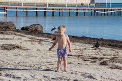 пристаньте воду к берегу каникулы камня взморья моря песка удерживания ребенка мальчика Стоковая Фотография