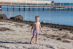 пристаньте воду к берегу каникулы камня взморья моря песка удерживания ребенка мальчика Стоковые Фотографии RF