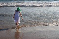 пристаньте девушку к берегу дня меньшяя смотря вода стоковое изображение