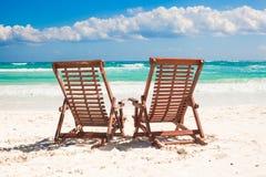 Пристаньте деревянные стулья к берегу на каникулы и ослабьте дальше Стоковое Изображение RF