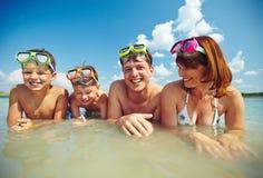 пристаньте детенышей к берегу тропической каникулы песка семьи 4 белых стоковое изображение