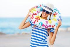Пристаньте женщину счастливую и красочные нося солнечные очки и шляпу к берегу пляжа имея потеху лета во время каникул праздников Стоковые Изображения