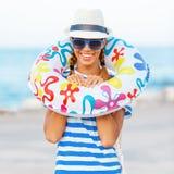 Пристаньте женщину счастливую и красочные нося солнечные очки и шляпу к берегу пляжа имея потеху лета во время каникул праздников Стоковая Фотография RF