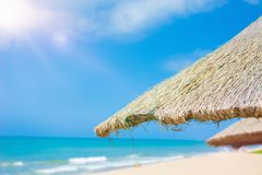 Пристаньте красивые покрыванные соломой зонтики к берегу и яркое море бирюзы, большое воссоздание и релаксацию рай тропический стоковые фотографии rf
