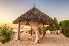 Пристаньте кресла для отдыха к берегу на заходе солнца, Занзибар, Танзанию Стоковые Изображения