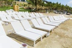 Пристаньте к берегу с белыми sunbeds в ряд на песчаном пляже Стоковая Фотография